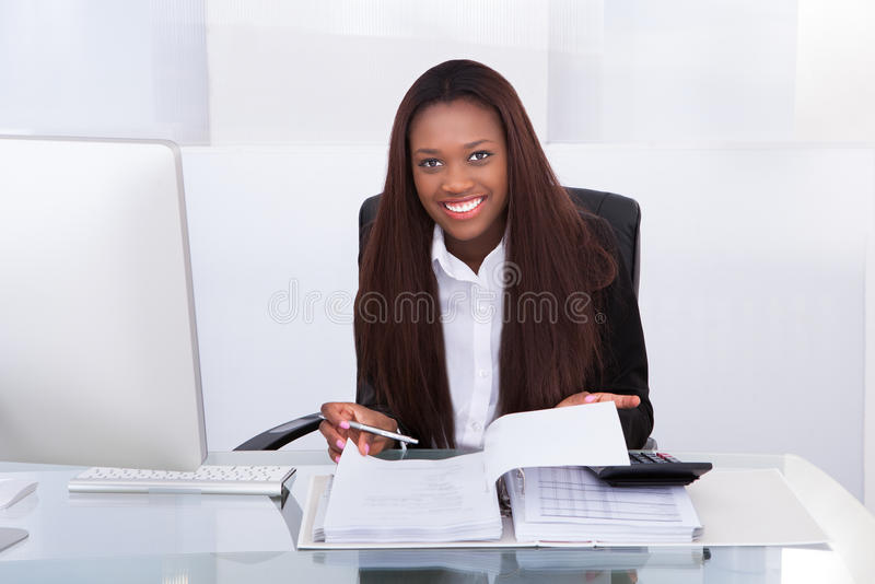 Confident businesswoman calculating tax at desk stock image