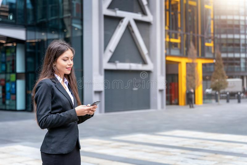 A businesswoman reads her emails on a mobile device in the City of London district stock photo