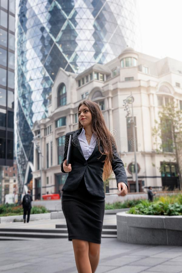 Businesswoman walks in the financial district of the City of London, UK royalty free stock photography