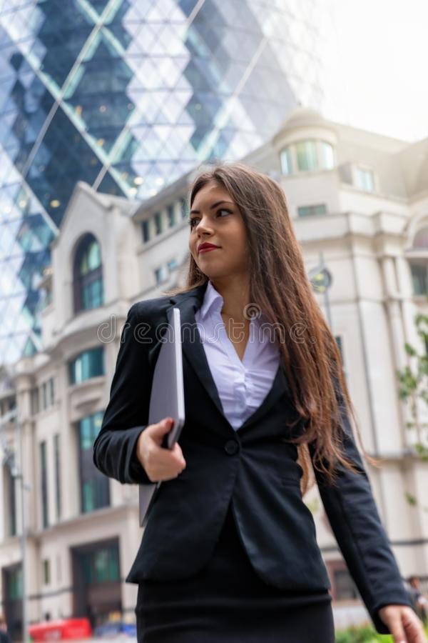 Confident businesswoman in corporate outfit walks outdoors in financial district. Confident, good looking businesswoman in corporate outfit walks outdoors in royalty free stock photo