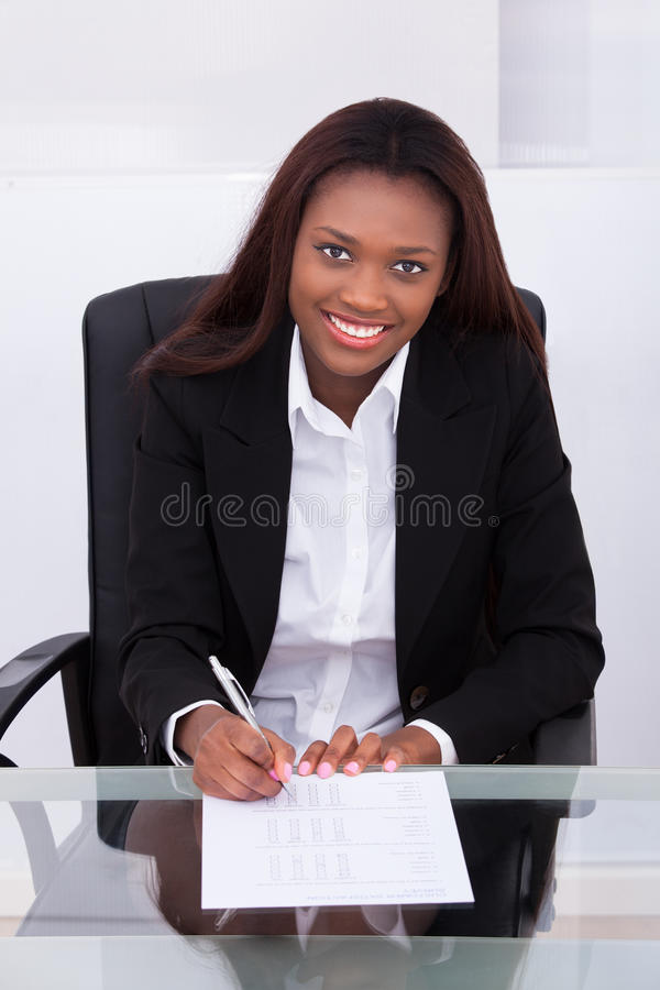 Confident businesswoman filling form at desk in office stock images