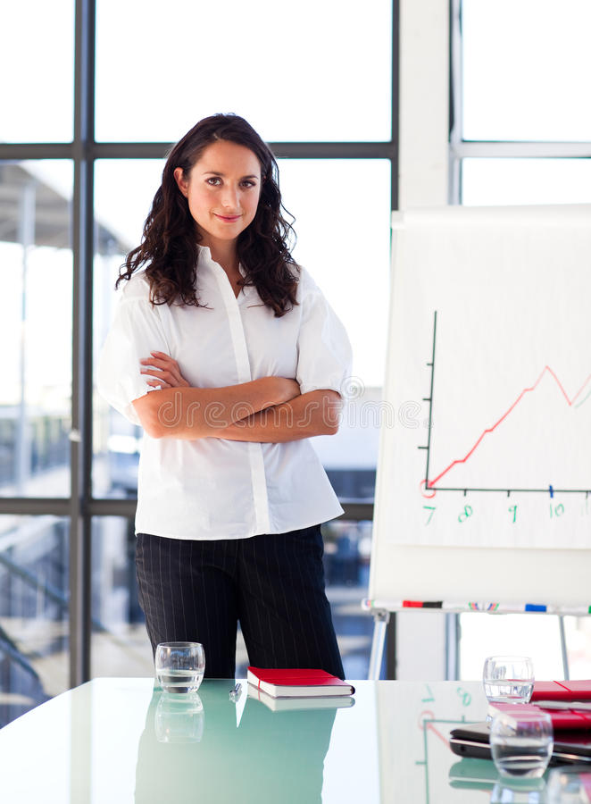 Confident businesswoman with folded arms. In a presentation royalty free stock image