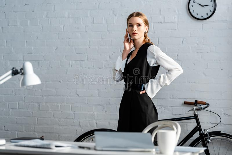 Confident businesswoman in formal wear talking on smartphone. In office stock photo