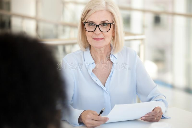 Confident businesswoman hold paper document, listen to colleague at meeting royalty free stock photos