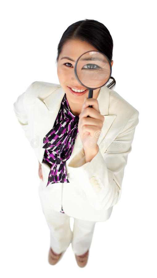 Confident businesswoman holding a magnifying glass royalty free stock photo