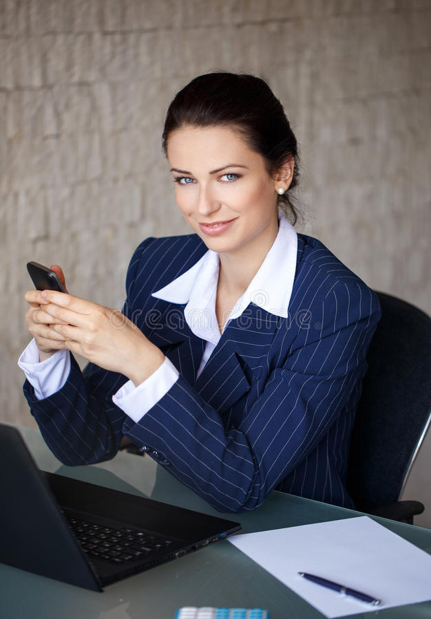 Confident businesswoman messaging in office. Teeth smile stock photo