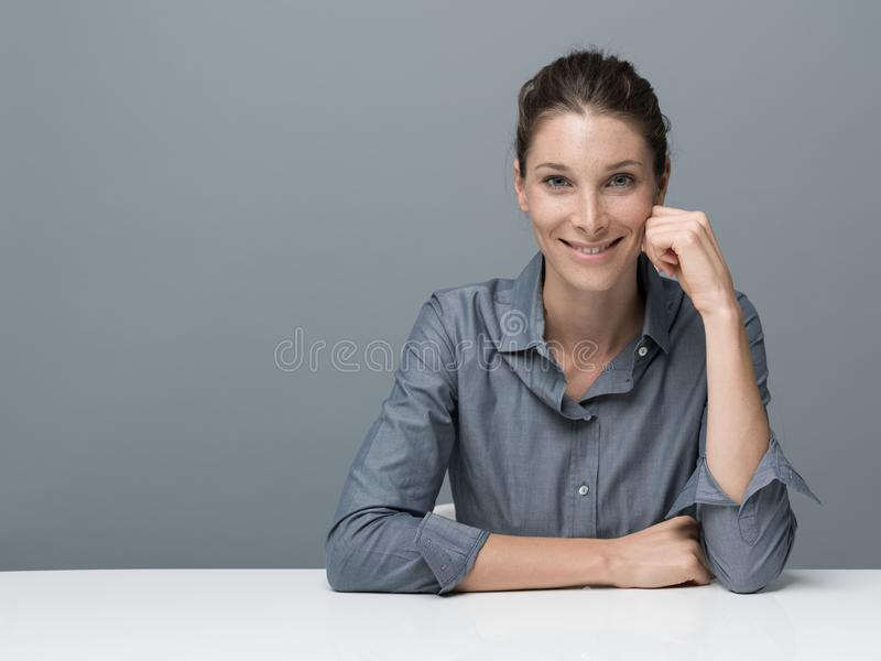 Confident businesswoman posing. Confident serene businesswoman sitting at desk and posing, she is smiling at camera stock photography