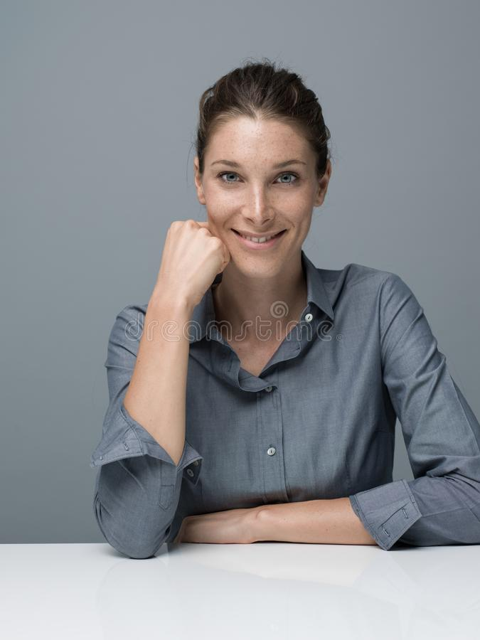 Confident businesswoman posing. Confident serene businesswoman sitting at desk and posing, she is smiling at camera stock photos