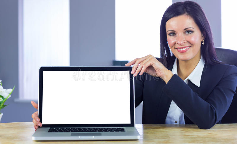 Confident businesswoman showing her laptop. In her office stock photography