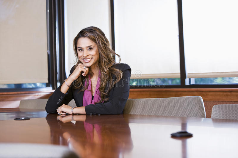 Confident businesswoman sitting in boardroom royalty free stock image