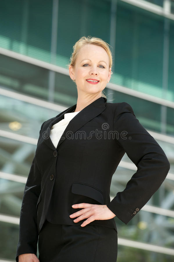 Confident businesswoman smiling outside office bui