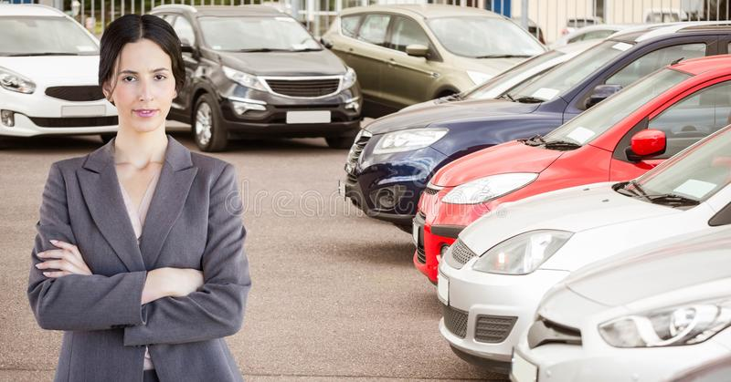 Confident businesswoman standing arms crossed in car showroom royalty free stock images