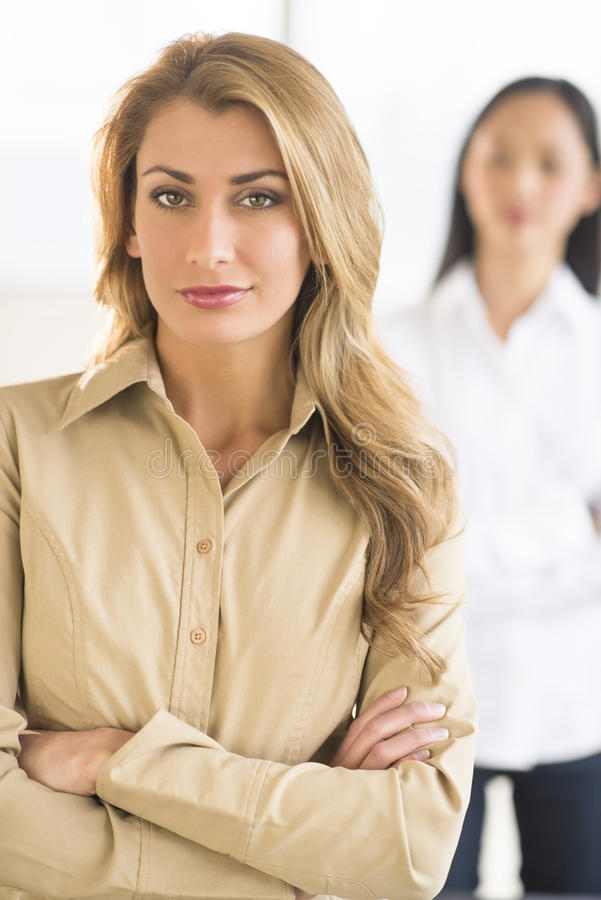 Confident Businesswoman Standing Arms Crossed In Office. Portrait of confident businesswoman standing arms crossed at office with female colleague in background stock photos