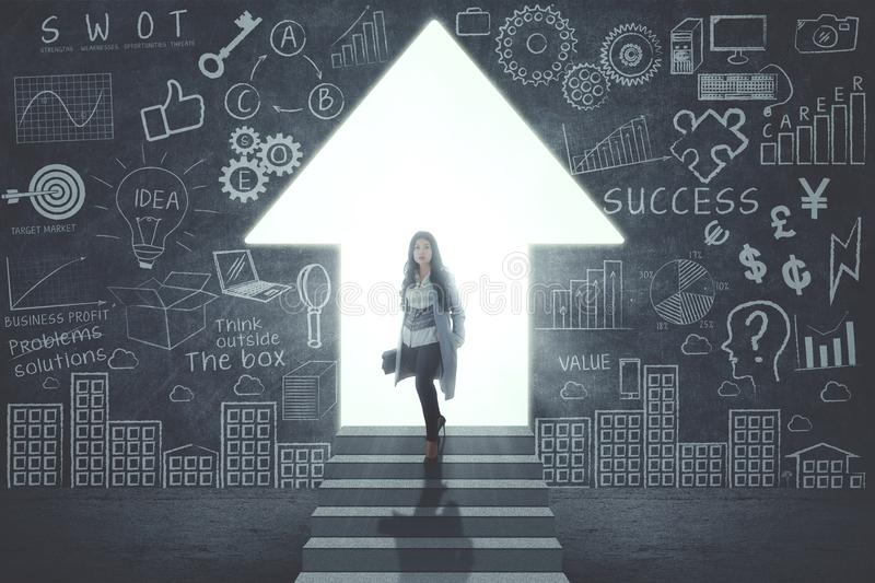 Confident businesswoman standing in front of door in form of up arrow. With success doodles on the wall royalty free stock photography
