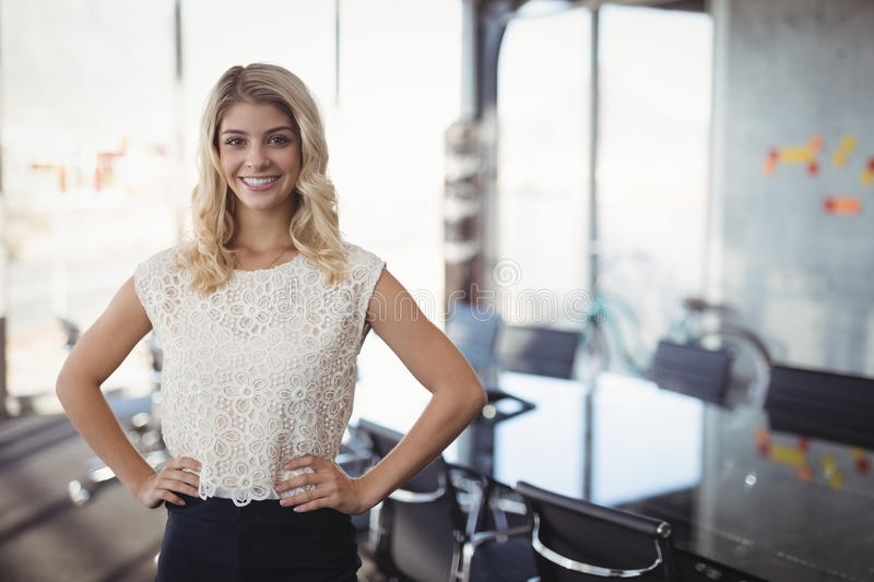 Confident businesswoman standing in meeting room at office royalty free stock photography