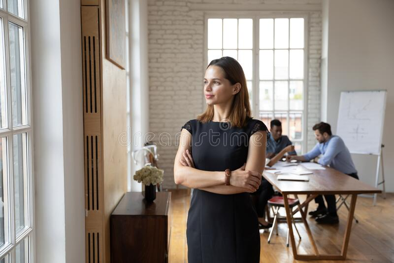 Confident businesswoman standing in office, looking through window royalty free stock images