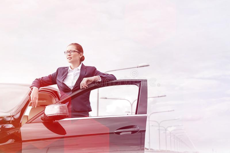 Confident businesswoman standing by open car door against sky stock photos