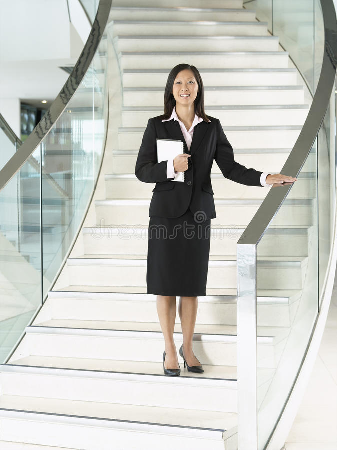 Confident Businesswoman Standing On Stairs. Full length portrait of a confident businesswoman with book standing on stairs royalty free stock photos