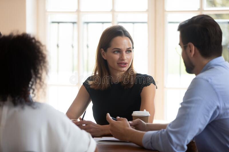 Confident businesswoman team leader holding briefing with diverse colleagues stock photography