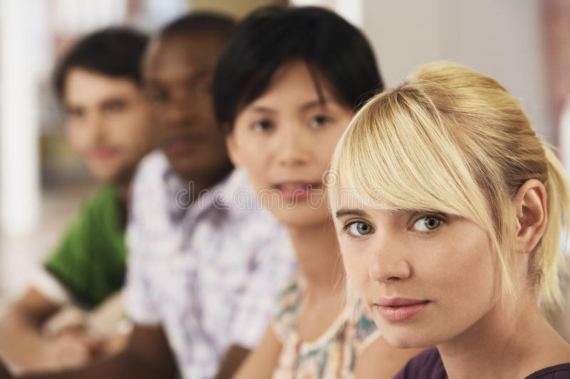 Confident Businesswoman With Team In Office. Closeup of confident businesswoman with team in background royalty free stock photography