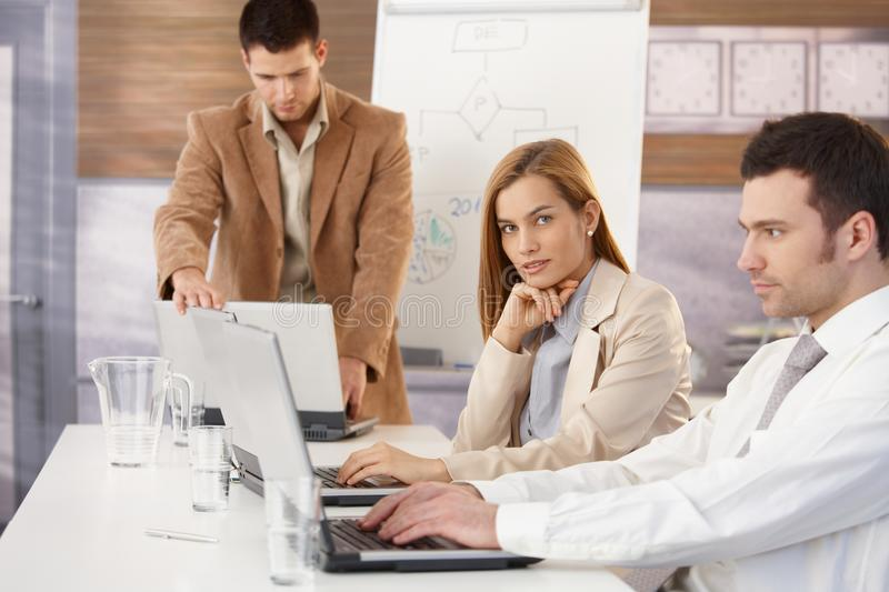 Confident businesswoman at training. Confident businesswoman sitting at business training with colleagues stock photography