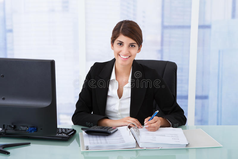 Confident businesswoman using calculator at office desk. Portrait of confident young businesswoman using calculator at office desk royalty free stock photo