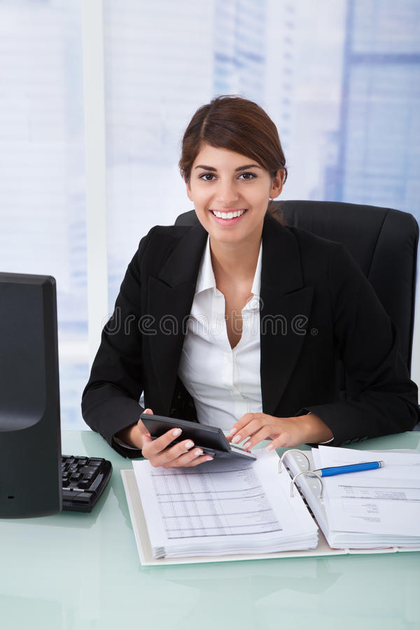 Confident businesswoman using calculator at office desk stock image