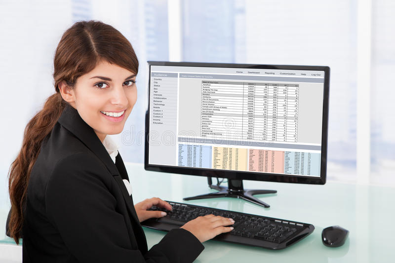 Confident businesswoman using computer at desk. Portrait of confident young businesswoman using computer at desk in office stock images