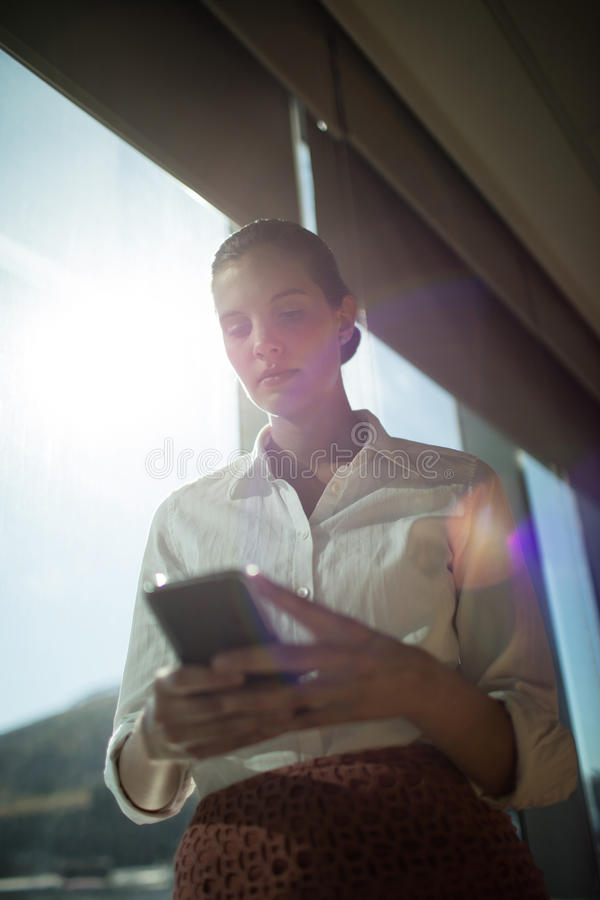 Confident businesswoman using mobile phone in office on sunny day royalty free stock photo