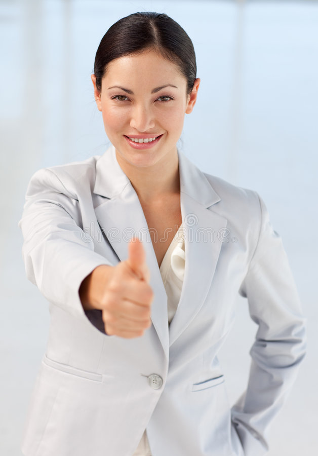 Confident busineswoman being positive. Confident and attractive busineswoman being positive with thumb up to camera stock photography