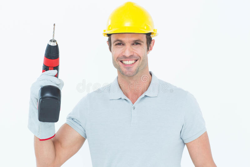 Confident carpenter holding cordless drill machine royalty free stock image