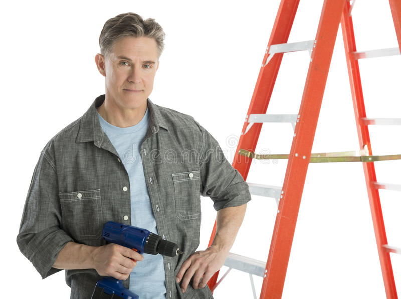 Confident Carpenter Holding Drill While Standing By Ladder. Portrait of confident male carpenter holding drill while standing by ladder against white background royalty free stock photography
