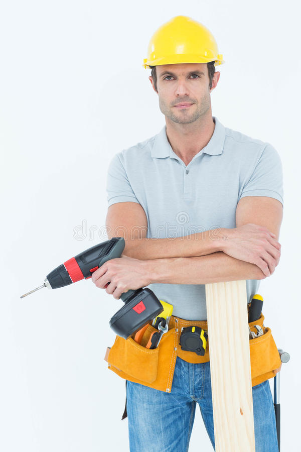 Confident carpenter with wooden plank and drill machine. Portrait of confident male carpenter with wooden plank and drill machine standing over white background royalty free stock image