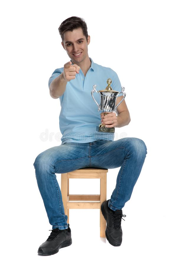 Confident casual guy pointing and holding a trophy. While smiling and wearing blue jeans and shirt, sitting on a chair on white studio background royalty free stock photo