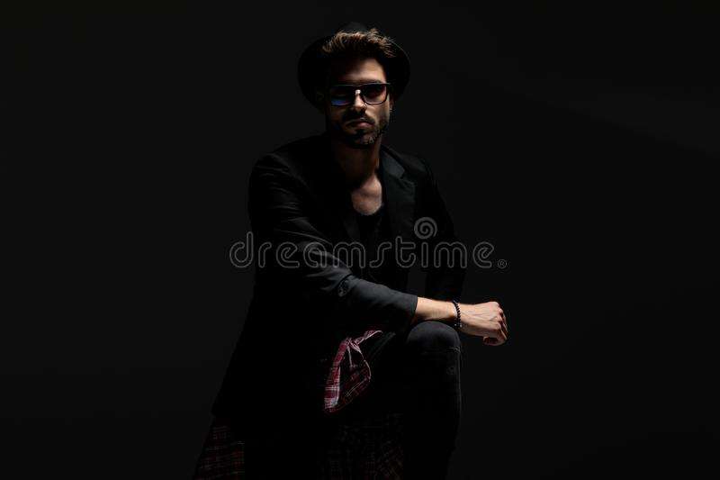 Confident casual man leaning on his leg while wearing sunglasses royalty free stock photography