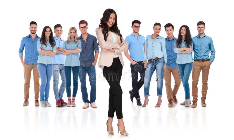 Confident casual team with businesswoman leader standing in front. Confident young casual team with businesswoman leader standing in front with crossed hands and royalty free stock photography