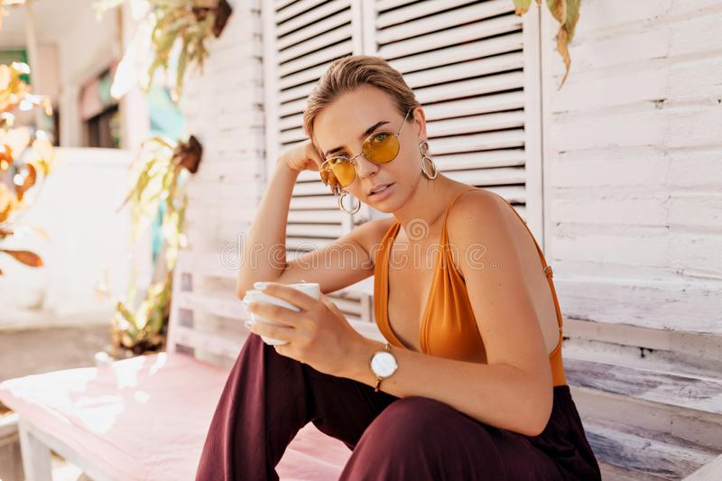 Confident caucasian blond woman in round summer glasses with coffee sitting on summer terrace in sunshine royalty free stock image