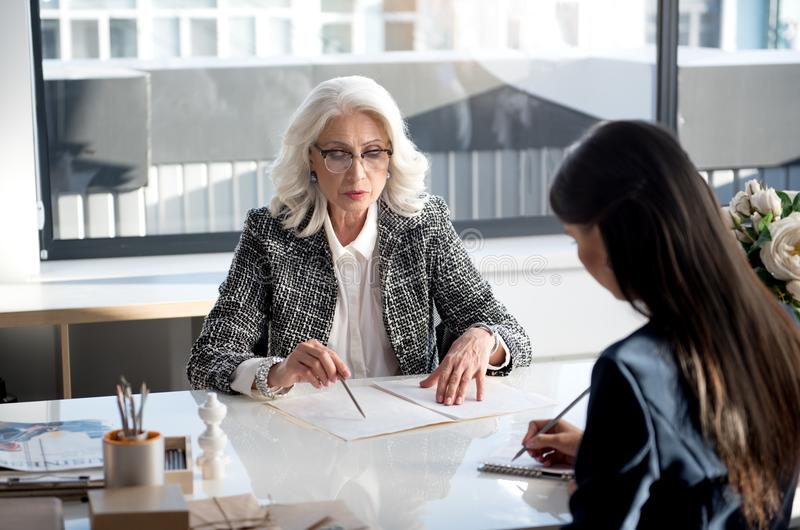 Confident charming women are laboring together in office. Important task list. Concentrated skillful senior female in glasses is sitting at desk with her royalty free stock photos