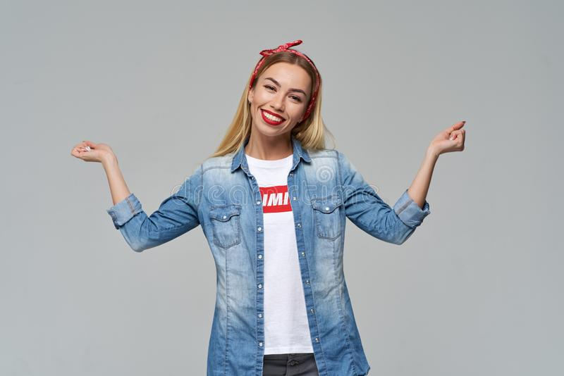 Confident cheerful and sociable young girl in casual denim clothes smiles cheerfully and raises her fists to the sides royalty free stock images