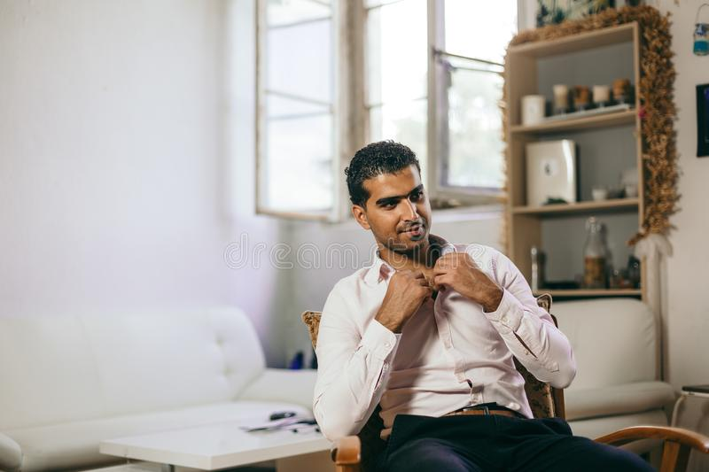 Confident and cheerful Syrian man is listening to a conversation. At his home royalty free stock photo