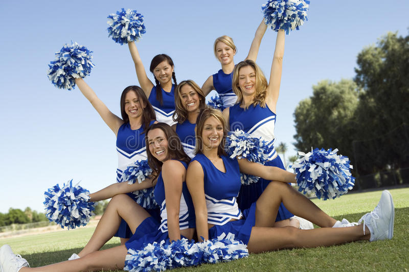 Confident Cheerleaders Holding Pompoms On Field royalty free stock image
