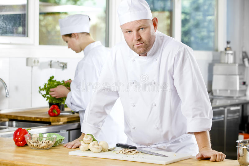Confident chef making food in large kitchen. Portrait of a professional male chef standing in the large kitchen. Female assistant or chef working in the stock photography
