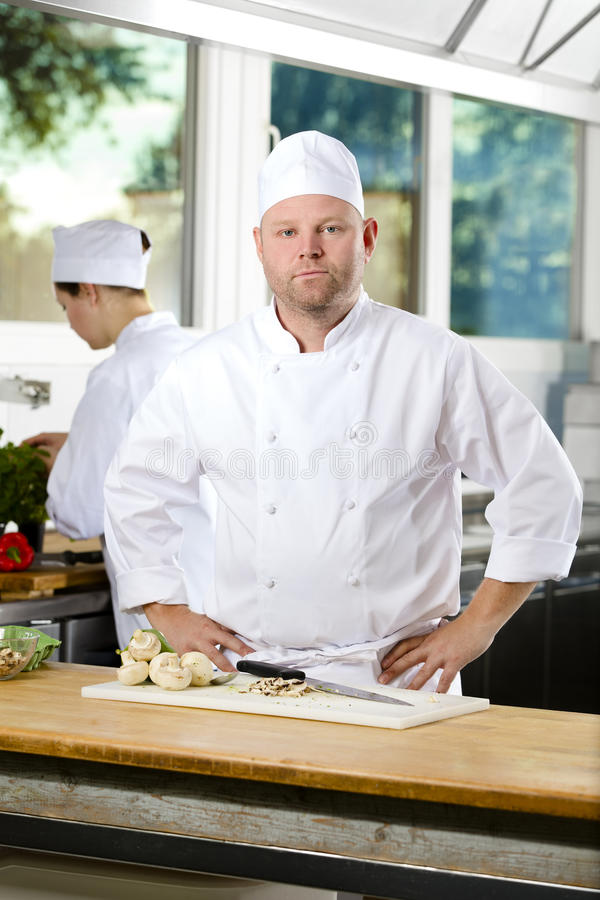 Confident chef standing in large kitchen. Portrait of a professional and smiling male chef standing in the large kitchen. Assistant working in the background stock photo