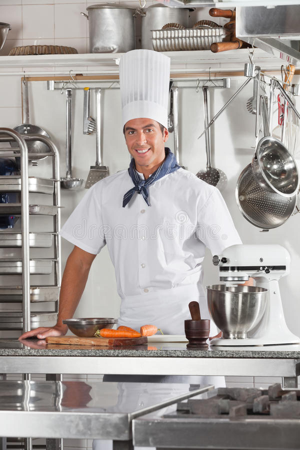 Confident Chef Standing In Restaurant Kitchen. Portrait of confident male chef standing at commercial kitchen counter royalty free stock image