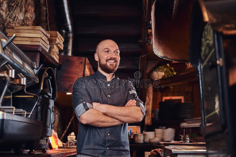 Confident chef posing with his arms crossed and looking away in a restaurant kitchen. stock photography