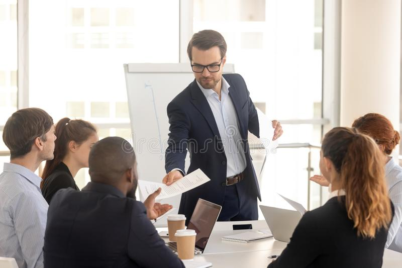 Confident coach giving handout to diverse seminar participants stock photos