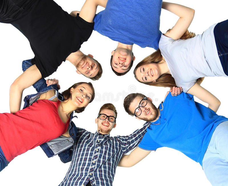 Confident college students forming huddle over white background royalty free stock photography