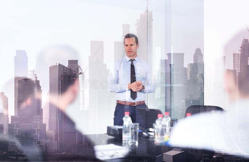 Confident company leader on business meeting against new york city manhattan buildings and skyscrapers window reflection royalty free stock images