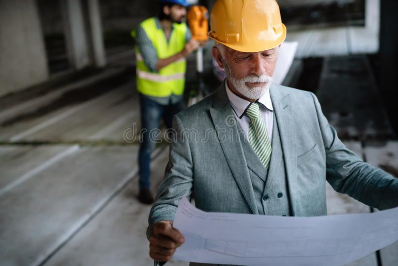 Confident construction engineer, architect, businessman in hardhat working on building site royalty free stock photos