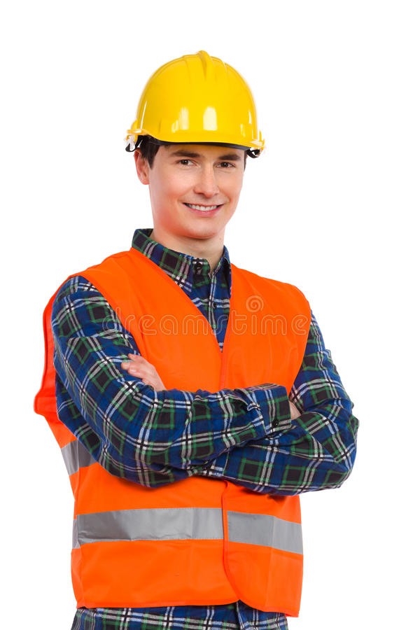 Confident construction worker with crossed arms. Smiling construction worker in yellow helmet and orange waistcoat. Waist up studio shot isolated on white royalty free stock image